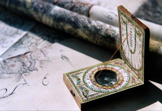 Sonnenuhr-Landkarten-Wandel-Wirtschaft: Foto einer sehr alten Taschensonnenuhr zum Aufklappen mit kleinem Kompass. Die Sonnenuhr steht auf einigen alten Landkarten.