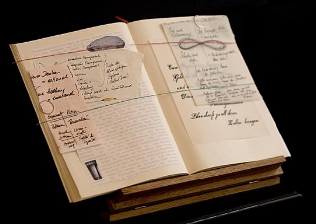 Coopers Tagebuch LILA Management Prinzip: Bild eines großen Buches, das auf einem Pult steht. Man erkennt Handskizzen und eingelegte Papiere.
