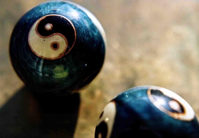 Yin Yang Kugeln . Ganzheitlichkeit Kresse-Wallner 2009: Foto von zwei Yin Yang Kugel auf einer gold-braunen Tischplatte. Die Kugeln sind dunkel-türkis mit einem weiß-schwarzem Yin Yang Symbol. Eine Kugel ist ganz zu sehen, die zweite nur zum Teil.