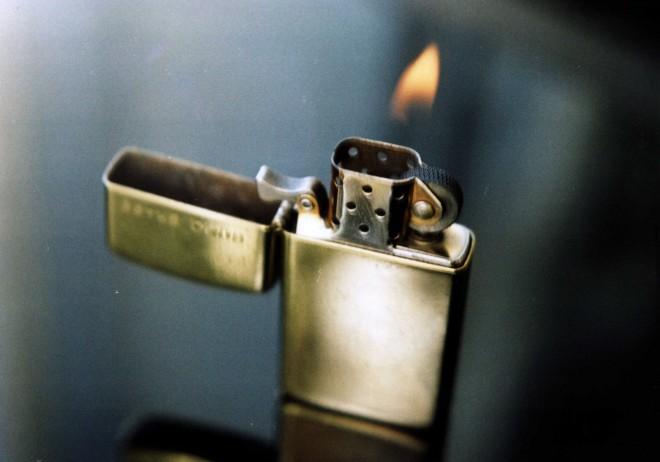 train the eight - feuer der Begeisterung - kresse-wallner 2009: Foto eines alten Zippo-Feuerzeuges mit Flamme. Das goldene Feuerzeug steht auf einem Tisch mit schwarzer, spiegelnder Platte.