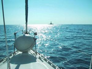 Im Leben ein Ziel haben: Das Bild zeigt ein Foto auf einem Segelboot in Kroatien. Vom Boot ist nur der Bug zu sehen. In der Ferne ist ein Felsen mit einem kleinen Leuchtturm zu erkennen. Das Wetter ist sonnig und wolkenlos.