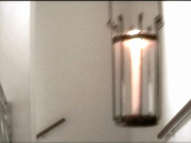 Bild einer Laterne mit einer brennenden Kerze. Die Laterne ist aus schwarzem Metall, das mit einem Glaszylinder ausgestattet ist. Man sieht nur die Laterne und im Hintergund ein Stiegenhaus.