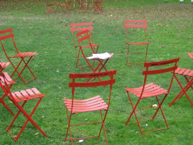 Kommunikation Sesselkreis: Das Bild zeit einen Rasen, auf dem rote einfache Klappsessel aufgestellt sind. Es war offensichtlich ein Sesselkreis, der nach dem Verlassen der TeilnehmerInnen nun etwas unordentlich aussieht.