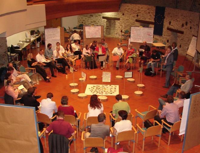 Großkreis PeerSpiritCicle: Foto einer Gruppe von ca. 40 Menschen, die im Kreis auf Sesseln sitzen und gemeinsam an einem Thema arbeiten. Rundum befinden sich Flipcharts und PIN Wände mit den Arbeitsergebnissen. Es ist ein DIALOG Format.