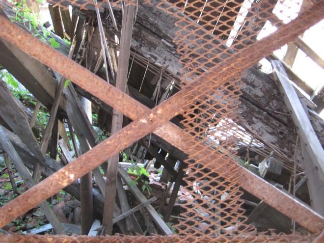 Das Foto zeigt die morschenden Reste eines Bauwerks auf Holz und Eisengittern. Es sind Bretter und Balken zu erkennen, die kreuz und quer übereinander liegen. Das Bauwerk ist eingestürzt. Die Natur beginnt sich das Gebiet zurückzuholen. Pflanzen dringen bereits ein.