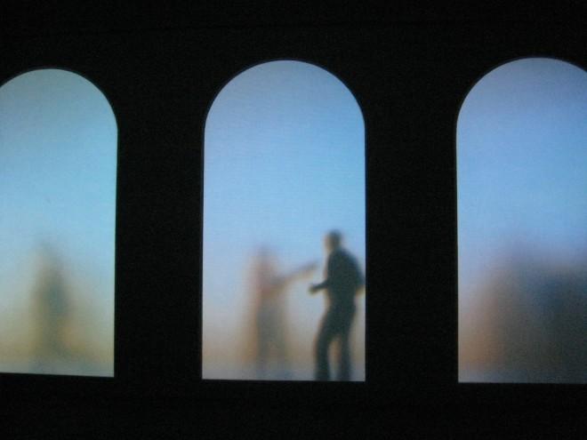 Krzysztof Wodiczko - Ospiti/Guests/Goscie - 2008/2009: Ein Kunstinstallation von Krzysztof Wodiczko. Auf dem Foto sieht man runde Torbögen. Dahinter sieht man durch eine Art Milchglas einige Menschen stehen. Es entsteht eine dunkle, sehr gedämpfte Szenerie.