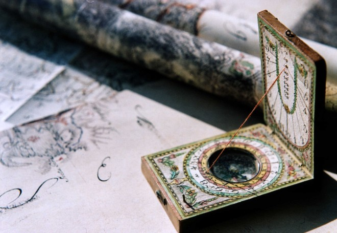 Selbstführung: Bild eines sehr alten Instrumentes, das Kompass und Sonnenuhr vereint. Der aufgeklappte Kompass steht auf alten Landkarten.