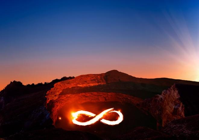 Und wofür brennen Sie? BILD - das Bild zeigt eine Aufnahme eines Vulkankraters. Das Feuer ist als liegende Acht dargestellt. Im Hintergrund ist ein blauer Himmel und ein Sonnenuntergang zu sehen. Es ist ein Marketingbild für das Konzept Train the eight.
