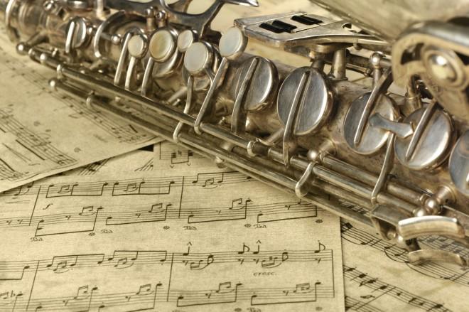 Source: iStock : Foto eines Blasinstrumentes. Man sieht nur einen Ausschnitt. Es dürfte sich um eine Klarinette aus Metall handeln, die auf Notenpapier liegt.