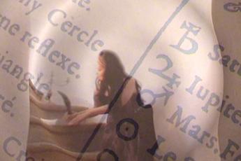 Madame Di Men Sion: Bild einer Frau mit langen schwarzen Haaren, die auf einer Steinstiege sitzt und eine Schreibfeder in der Hand hält. Über das Bild sind alte Texte gelegt, die alte Symbole enthalten. Das gesamte Bild macht einen mystischen Eindruck.