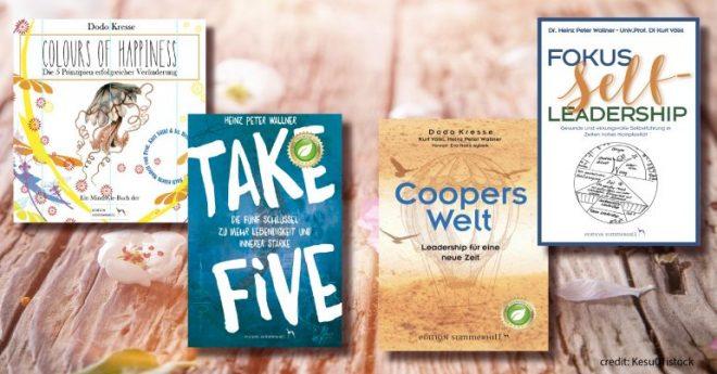 Das Bild zeigt vier Bücher des Verlages Edition Summerhill. Colours of Happiness, Take Five, Coopers Welt, Fokus Selfleadership. Die Bücher sind auf einem alten Holzboden aufgelegt.