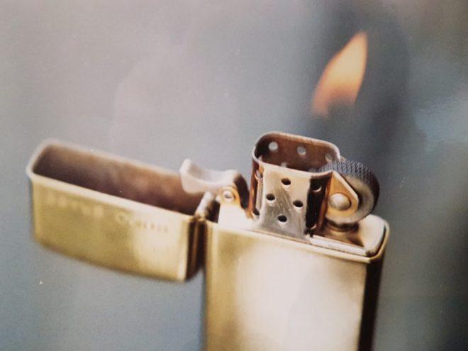 Altes Gasfeuerzeug aus Messing mit brennender Flamme. Das Feuerzeug ist von der Marke Zippo. Der Hintergrund des Bildes wirkt grau, weil er unscharf ist.