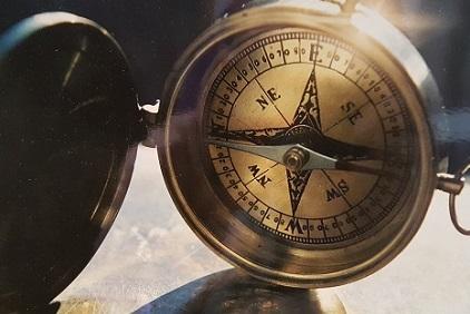 Kompass - Foto von Dodo Kresse: Alter Kompass aus Messing mit aufgeklapptem Deckel. Der Kompass ist aufgestellt, sodass er sich zeigt, wie eine Uhr. Der Untergrund wirkt ebenso metallisch glänzend. Am oberen rechten Teil spiegelt sich das Licht.