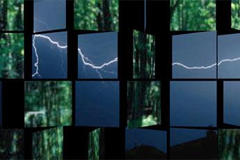 Das Bild zeit eine Wand, die aus großen Würfeln besteht. Die Würfel können sich auf einer vertikalen Achse drehen. Einige Würfel zeigen ein Bild eines grünen Waldes, andere einen Himmel voller Blitze. Die unterschiedliche Verdrehung der Würfel macht das Bild interessant.