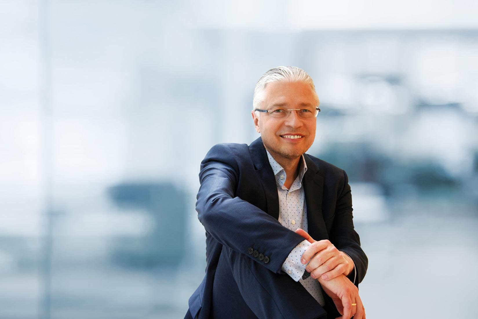 Das Bild zeigt Dr. Heinz Peter Wallner in einer sitzenden Position. Er trägt ein blaues Hemd und einen klassischen dunkelblauen Businessanzug. Der Hintergrund ist unscharf und daher nicht genau zu erkennen. Heinz Peter Wallner trägt eine Brille ohne Rahmen.