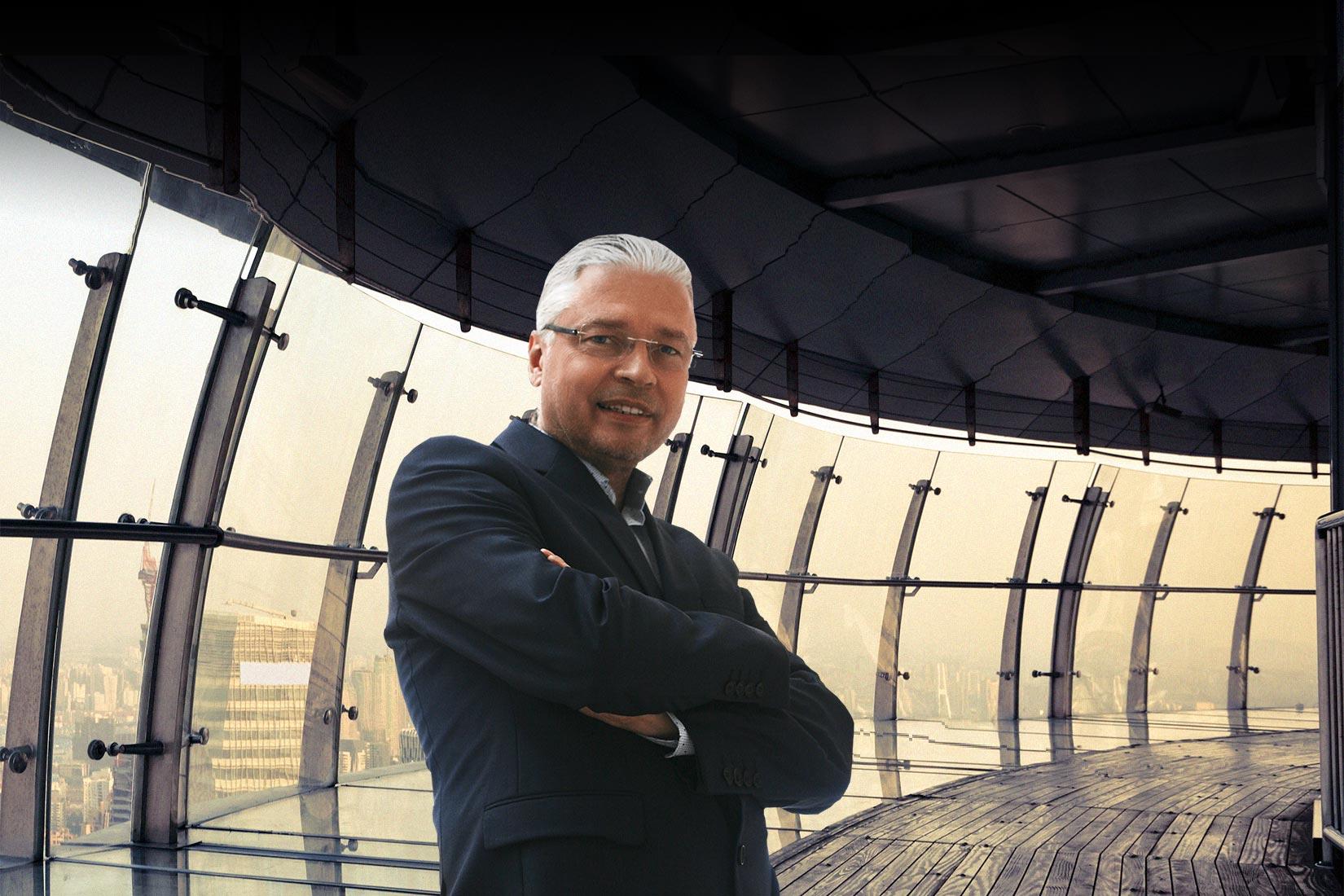 Das Foto zeigt Dr. Heinz Peter Wallner stehend in einem blauen Anzug mit verschränkten Händen. Er lehnt an einem Geländer auf dem Dach eines Wolkenkratzers in einer Stadt in China. Im Hintergrund sieht man durch die Glasflächen die Skyline der Stadt.
