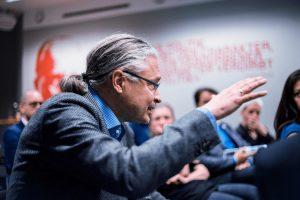 Das Bild zeigt Dr. Heinz Peter Wallner sitzend in einem Plenum in einer angeregten Diskussion. Er argumentiert und gestikuliert mit den Händen. Er ist von der Seite zu sehen.